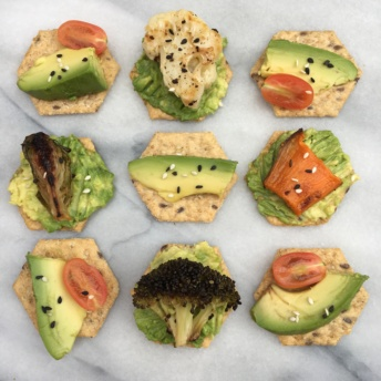 Gluten-free crackers topped with avocado and veggies