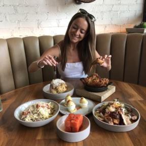 Jackie eating fried chicken and cauliflower at Yardbird