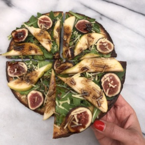 A slice of gluten-free KBosh Food zucchini pizza crust with pears, figs, and balsamic