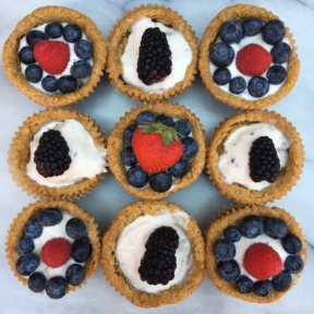 Gluten-free chocolate chip cookie cups filled with ice cream and berries