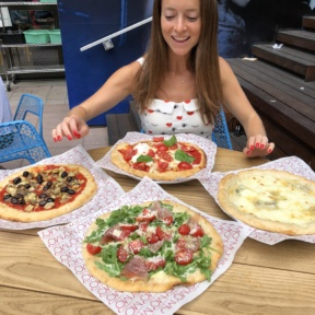 Jackie deciding which pizza to eat first at Ribalta Mo