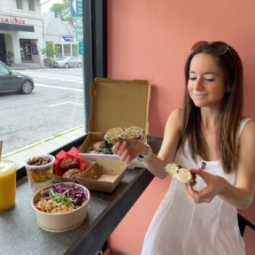 Jackie eating gluten-free bagel at Root2Rise NY